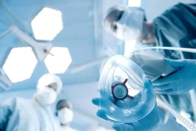 Mittlerweile sind die Kliniken wieder voll mit Corona-Patienten, und das Personal kommt ans Limit: Ein Anästhesist setzt einem Patienten eine Sauerstoffmaske auf.