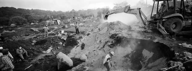 Angehörige von Vulkanopfern beobachten Rettungsversuche und Bergungsarbeiten mit einem Bulldozer.