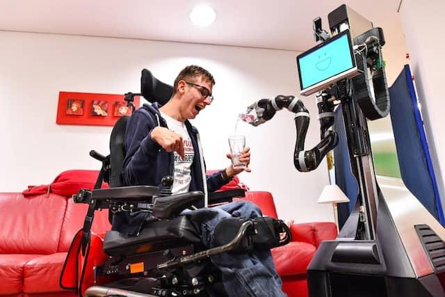 Roboter Marvin schenkt seinem körperbehinderten Namensvetter Marvin Thurner bei einer Präsentation ein Glas Wasser ein.
