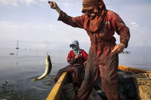In Schutzkleidung aus den Beständen der staatlichen Fördergesellschaft PDVSA angeln Männer den örtlichen Barsch Robalo.
