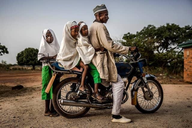 """Ein Vater bringt seine Töchter zum Unterricht in die """"Wuro Fulbe Nomadic School"""" in Kacha."""