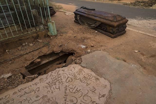 Ein oxidierter Sarg liegt neben einem Grab, das von Dieben auf einem Friedhof in Maracaibo ausgegraben wurde. Oft plündern Diebe die Gräber in der Hoffnung, darin Wertgegenstände zu finden.