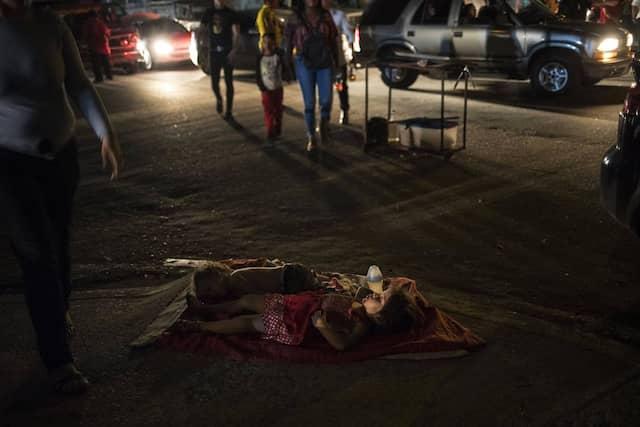 Kinder schlafen auf der Straße in der Nähe des Essensstandes ihrer Mutter, wo sie Lebensmittel verkauft.