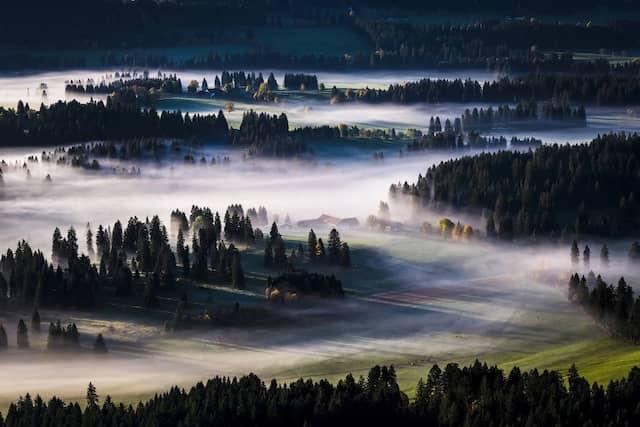 Morgendlicher Nebel zeigt sich bei Les Bois im Schweizer Jura.