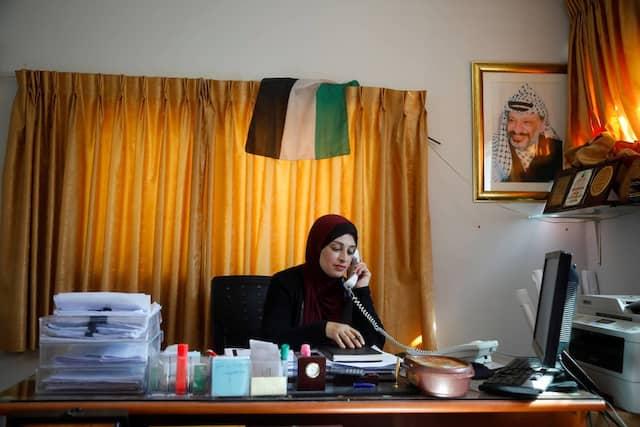 """Die Palästinenserin Bothena Turabe, Stadträtin der Stadt Sarra telefoniert an ihrem Arbeitsplatz zuhause. Sie sah die benachbarte Siedlung Havat Gilad über Jahre wachsen. """"Nachts blickst Du hinüber, und Du denkst , dort ist nichts, am nächsten Morgen stehen weitere Caravans dort"""". Sie sagt, es sei nicht das Land Israels, die Israelis hätten es gestohlen."""