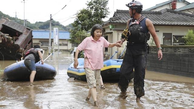 In Hitoyoshi retten zwei Helfer eine Frau. Schwere Regenfälle haben in Südjapan zu Erdrutschen geführt.