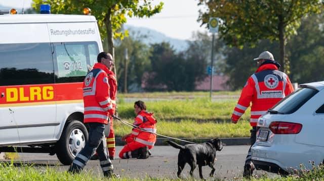 Bayern, Furth im Wald: Einsatzkräfte mit einem Suchhund stehen auf einem Parkplatz an der deutsch-tschechischen Grenze.