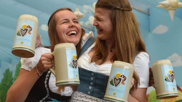 Frauen in Dirndln präsentieren Ende August die neuen Oktoberfest-Krüge.