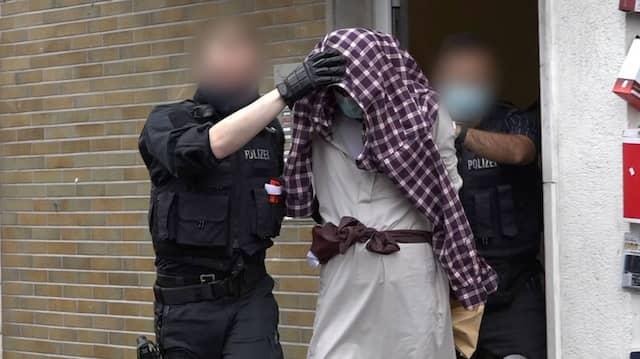 Hagen: Ein Mann wird im Zusammenhang mit dem mutmaßlich geplanten Anschlag auf die Hagener Synagoge von Polizisten abgeführt.