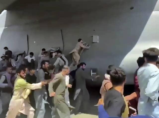 """Verzweifelte Afghanen klammern sich am 16. August am Kabuler Flughafen an ein Flugzeug der Air Force: Auch dieses """"bittere Finale"""" des Afghanistan-Einsatzes werde das Bild der amerikanischen Verlässlichkeit nicht nachhaltig beschädigen, glaubt Kupchan"""