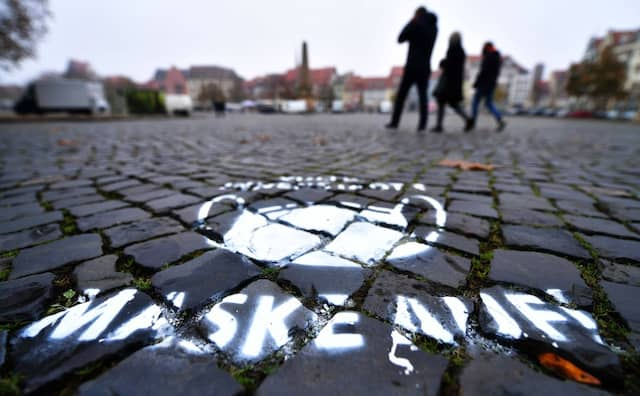 """Die Aufforderung """"Maske auf"""" wurde in Erfurt auf den Boden eines Platzes gesprüht."""
