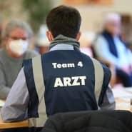 Eine Pflegerin wird vom Mediziner Frank Ummendorfer vom Zentralen Impfzentrum in Tübingen aufgeklärt.