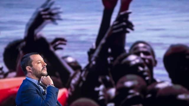 Matteo Salvini 2018 während einer Fernsehsendung des Senders RAI, während im Hintergrund ein Bild von Migranten gezeigt wird, die auf See gerettet werden.