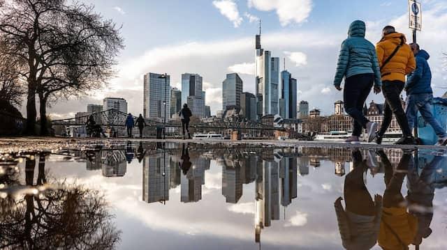 Parallelwelt: Ein Teil der Frankfurter Skyline spiegelt sich in einer Pfütze am Mainufer.