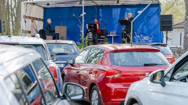 Frühlingsstimmen: drei Musiker spielen vor 70 Autos