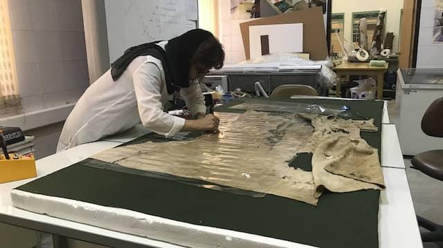 Handarbeit: Eine Mitarbeiterin des iranischen Instituts RCCR restauriert eine 1500 Jahre alte Tunika aus dem Salzbergwerk von Zanjan – wann die in Frankfurt zu sehen sein wird, ist offen