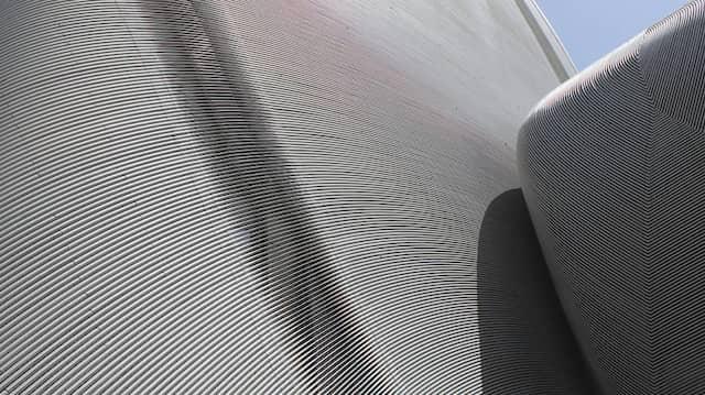 Hinter der futuristischen Metallfassade verbergen sich rund 4.000 Quadratmeter ebenfalls frei geformte Glasscheiben.