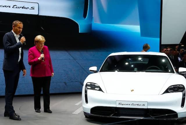 """Angela Merkel am Porsche-Stand: Dort erklärte ihre Porsche-Chef Oliver Blume, dass Produktion und Bestellungen des Vorzeige-Elektromodells Taycan sich auf jeweils 30.000 Stück beliefen. """"Also ein Jahr  Wartezeit"""", folgerte Merkel. Als Blume antwortete: """"Wir machen's exklusiv"""", lehnte sie dankend ab: """"Ok. Ich hatte nicht vor, einen zu kaufen."""""""