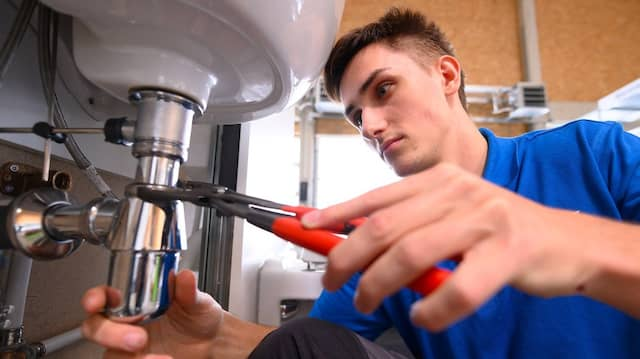 Auszubildender arbeitet in Dresden an einer Übungswand mit einer Rohrzange an einem Waschbecken.