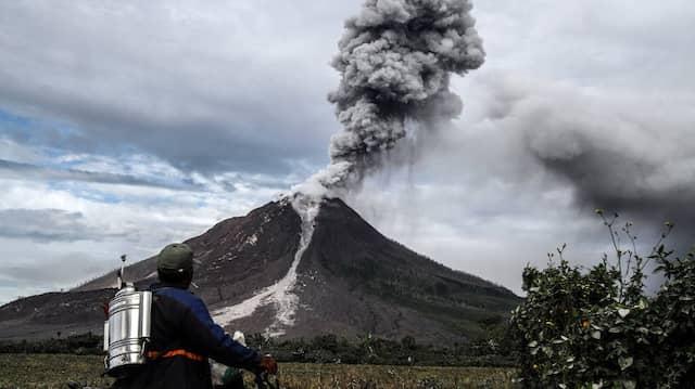 Ein indonesischer Bauer beobachtet eine Rauchsäule über dem Vulkan Mount Sinabung. Zahlreiche Bewohner aus der Umgebung des seit über 400 Jahren wieder ausgebrochenen Vulkans sind in Sicherheit gebracht worden.