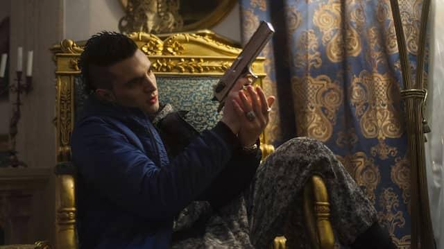 """Der Narr auf dem Thron, die Waffe im Anschlag: Giacomo Ferrara in einer Szene von """"Suburra""""."""
